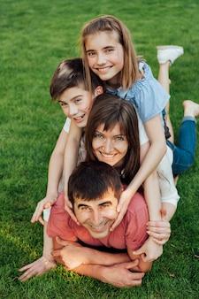 Retrato de la familia feliz que pone en hierba en el parque