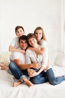 Retrato de familia feliz sentado en la cama en su casa