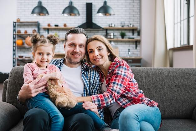Retrato de familia feliz sentado en el sofá