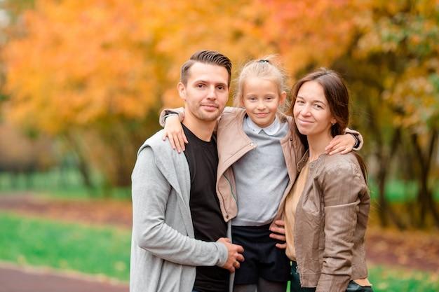 Retrato de familia feliz de tres en día de otoño