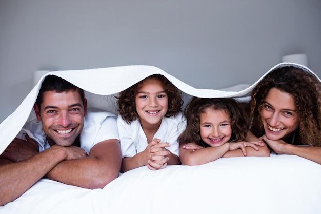 Retrato de familia feliz tumbado debajo de una sábana