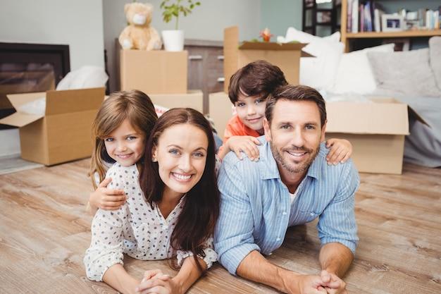 Retrato de familia feliz tumbado en el piso de madera
