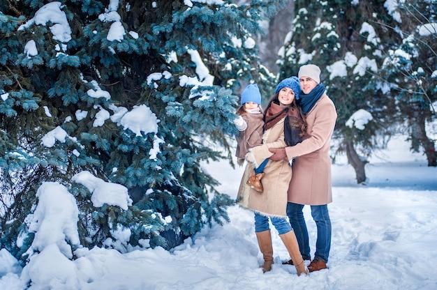 Retrato de una familia en el fondo de árboles cubiertos de nieve en el bosque