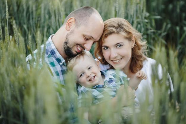Retrato de familia hermosa entre el campo de trigo