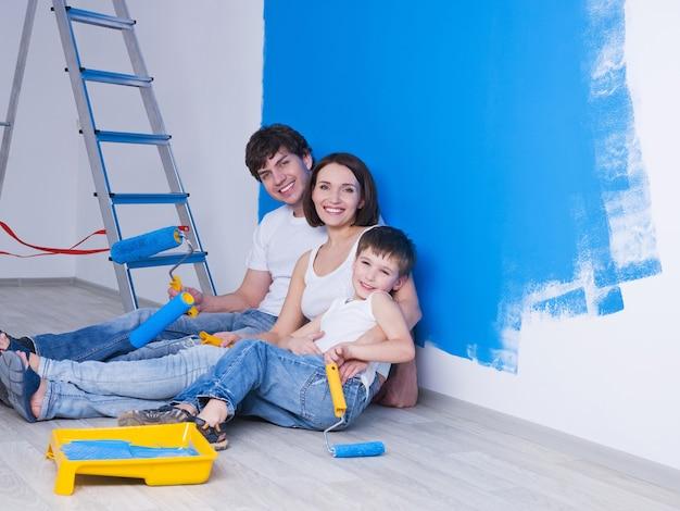 Retrato de familia joven feliz con hijo pequeño sentado cerca de la pared pintada