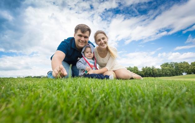 Retrato de familia joven feliz con niño de 9 meses relajándose sobre el césped en el parque