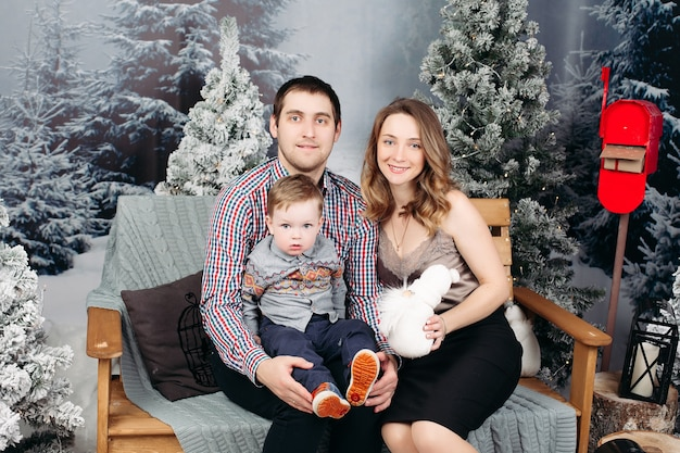 Retrato de familia joven feliz sentados juntos en un banco durante la navidad en el estudio, posando, sonriendo y mirando al frente