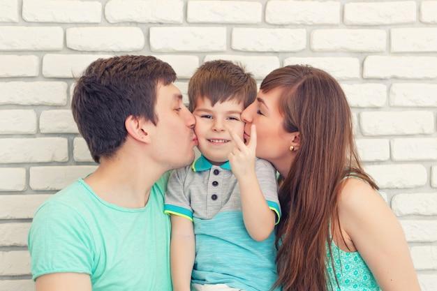 Retrato de familia joven feliz y sonriente sobre fondo de pared de ladrillo. padre y madre con niño pequeño. padres con niño