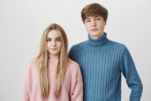 Retrato de familia de la joven pareja caucásica en suéteres. el niño rubio y la niña de ojos azules miran con expresiones tranquilas y complacidas