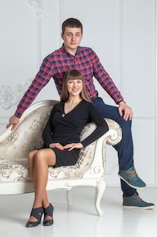 Retrato de familia de la joven pareja sentada en un sofá