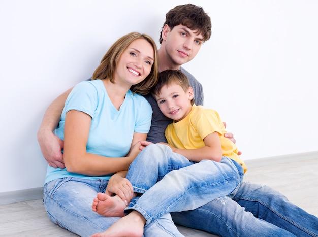 Retrato de familia joven riendo feliz con hijo pequeño - en el interior