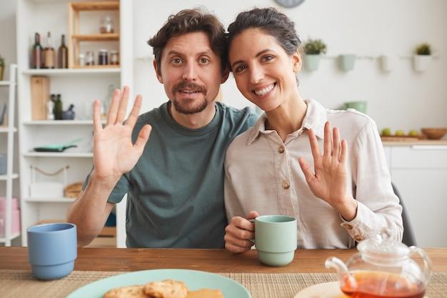 Retrato de familia joven sonriendo y saludando mientras está sentado a la mesa y desayunando en la cocina