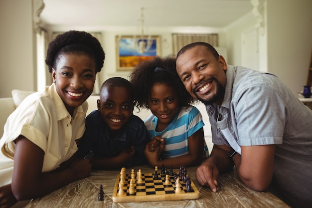 Retrato de familia jugando al ajedrez juntos en casa en la sala de estar