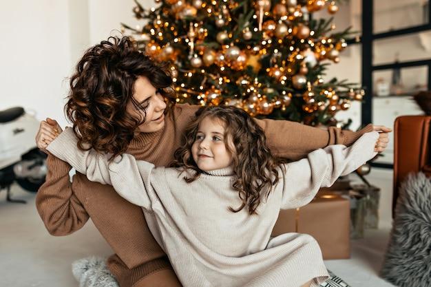 Retrato de familia de madre joven feliz y linda hija encantadora divirtiéndose y celebrando la fiesta de navidad con regalos