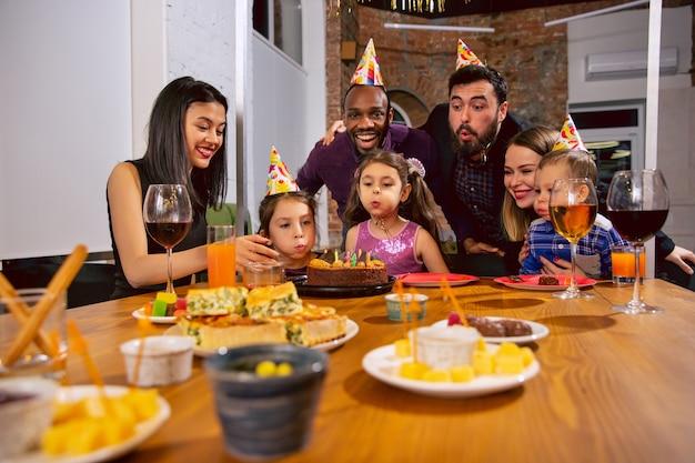 Retrato de familia multiétnica feliz celebrando un cumpleaños en casa. gran familia comiendo bocadillos y bebiendo vino mientras saluda y se divierte a los niños. celebración, familia, fiesta, concepto de hogar.