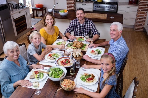 Retrato de familia multigeneración con comida en la cocina