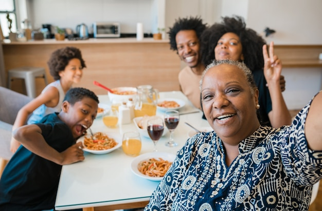 Retrato de familia multigeneracional afroamericana tomando un selfie juntos mientras cenan en casa.