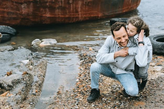 Retrato de familia de papá e hija con impermeable cerca del mar.