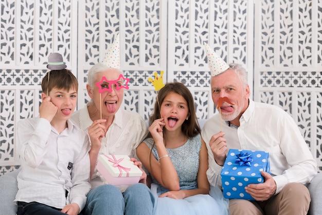 Retrato de una familia que sostiene apoyos de fiesta y cajas de regalo que salen de la lengua