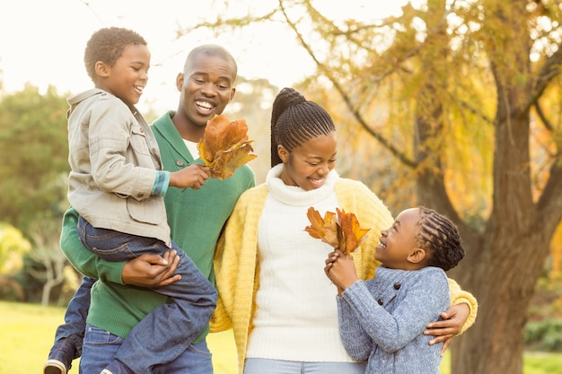 Retrato de una familia sonriente joven sosteniendo hojas
