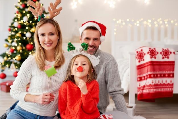 Retrato de familia sonriente en máscaras de navidad
