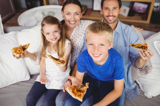 Retrato de familia sonriente sosteniendo rebanadas de pizza mientras está sentado en el sofá