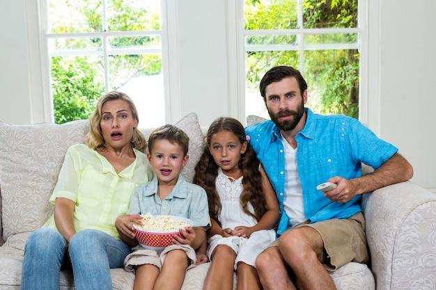 Retrato de familia sorprendida riendo mientras mira tv