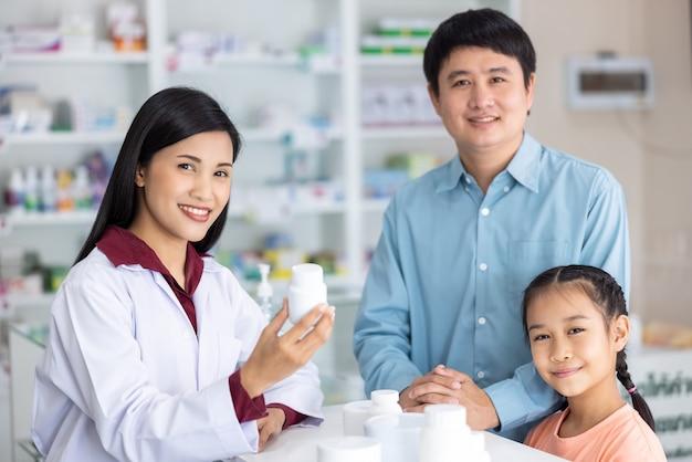 Retrato de farmacéutico y paciente mira cámara y sonriendo en farmacia