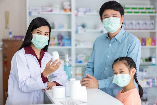 Retrato de farmacéutico y paciente mirando cámara y sonriendo en farmacia tailandia
