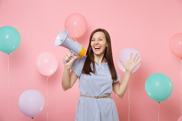 Retrato de fascinante joven feliz con vestido azul con megáfono extendiendo las manos sobre un fondo rosa brillante con coloridos globos de aire. fiesta de cumpleaños, gente sincera emot