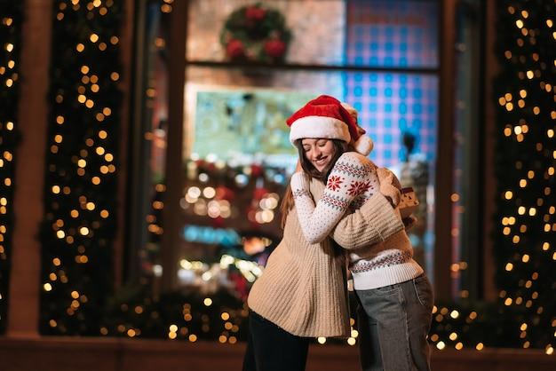 Retrato de felices lindos jóvenes amigos abrazándose y sonriendo mientras camina en la víspera de navidad al aire libre.