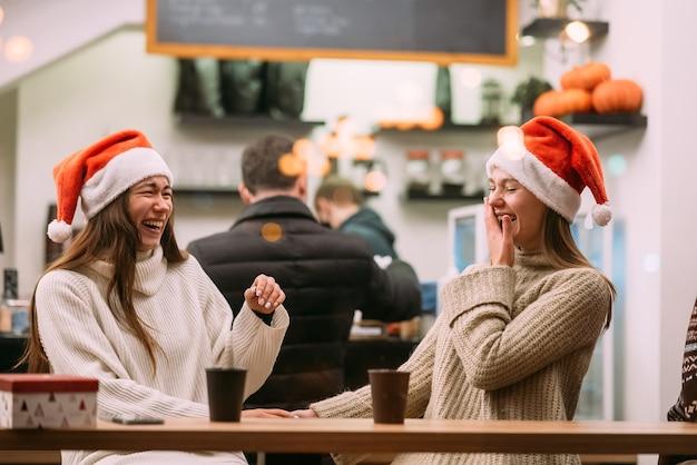 Retrato de felices lindos jóvenes amigos divirtiéndose en el café