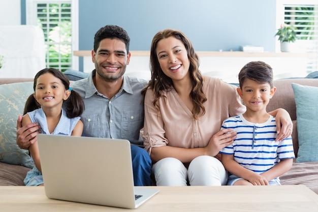 Retrato de felices padres y niños sentados con el brazo alrededor en la sala de estar