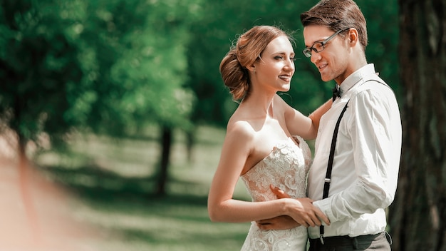 Retrato de felices recién casados en el fondo del parque de primavera