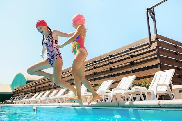 El retrato de felices sonrientes hermosas chicas adolescentes en la piscina