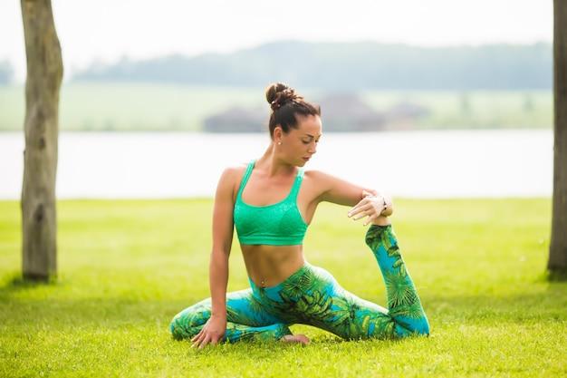 Retrato de felicidad joven practicando yoga al aire libre