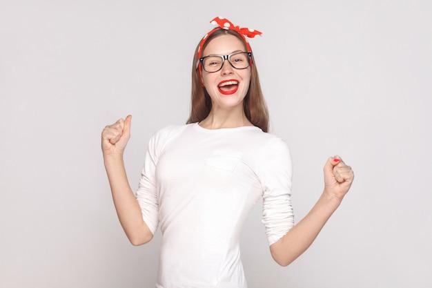Retrato de felicidad y victoria de hermosa mujer joven emocional en camiseta blanca con pecas, gafas negras, labios rojos y banda para la cabeza. tiro del estudio de interior, aislado en fondo gris claro.