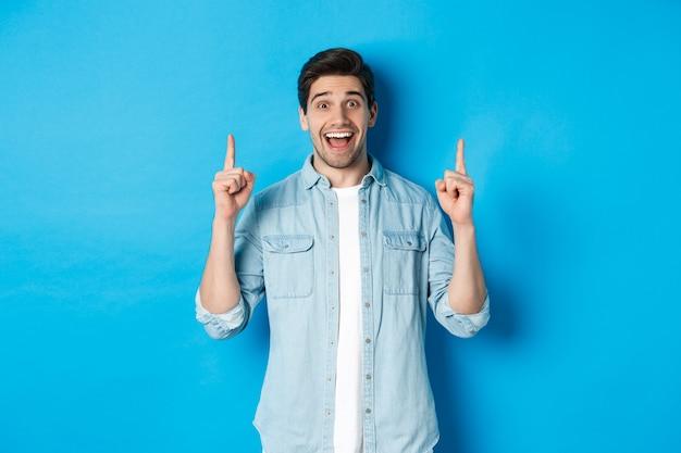 Retrato de feliz 25 años chico con barba, apuntando con el dedo hacia arriba y sonriendo, mostrando publicidad, de pie contra el fondo azul.