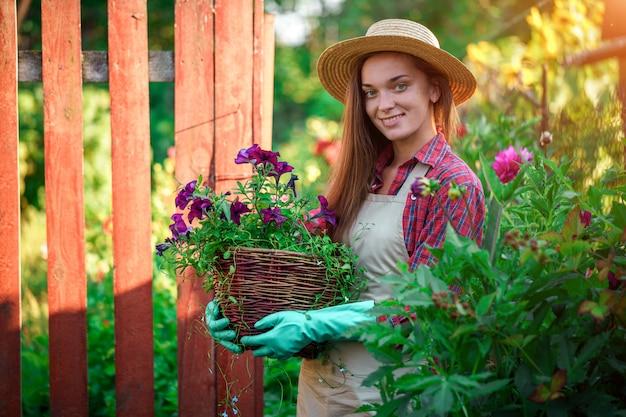 Retrato de feliz alegre florista jardinero con maceta de petunia al aire libre
