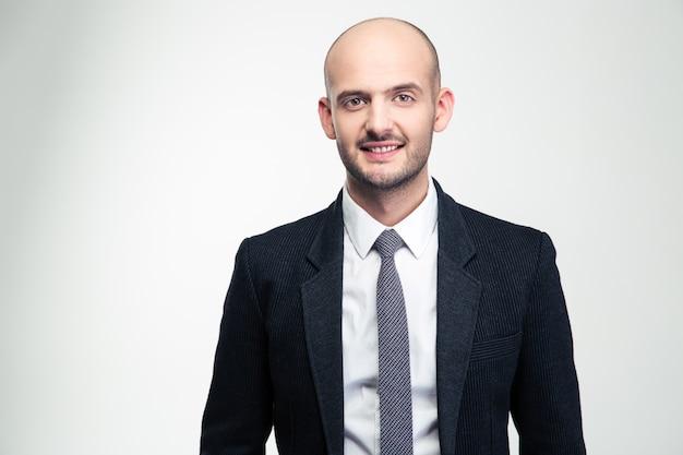 Retrato de feliz apuesto joven empresario en traje negro y corbata sobre pared blanca