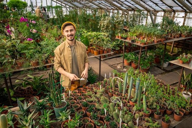 Retrato de feliz apuesto joven en gorra con llana pequeña mientras trabaja con plantas de cactus en invernadero espacioso