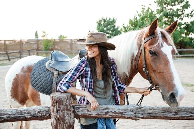 Retrato, de, feliz, atractivo, mujer joven, vaquera, con, caballo, en, rancho