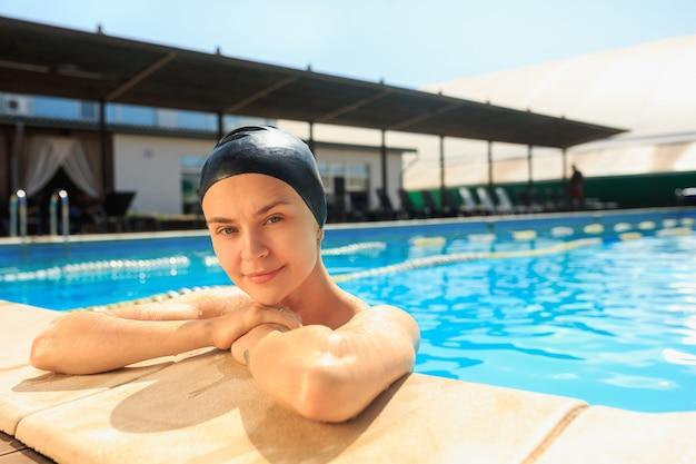 El retrato de feliz bella mujer sonriente en la piscina