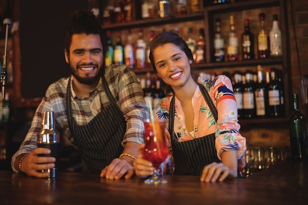 Retrato de feliz camarero y camarera de pie en el mostrador