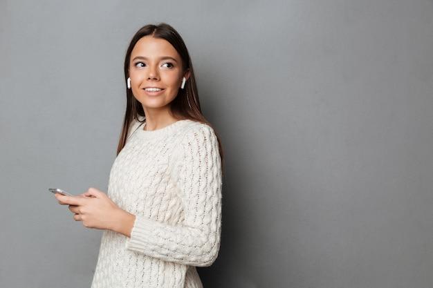 Retrato de una feliz chica atractiva en suéter