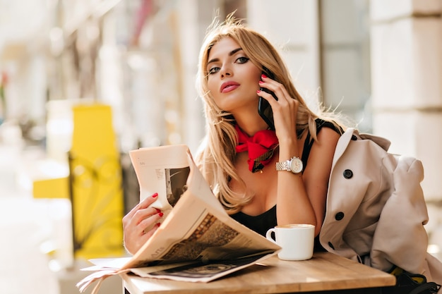 Retrato de feliz chica rubia descansando en la cafetería y hablando por teléfono con un amigo