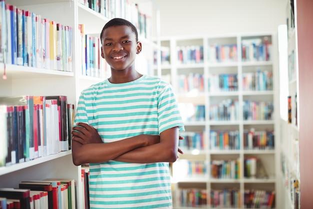Retrato de feliz colegial de pie con los brazos cruzados en la biblioteca