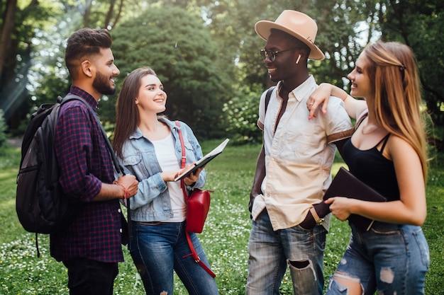 Retrato de feliz dos jóvenes y dos mujeres hablando al aire libre en la universidad en el campus