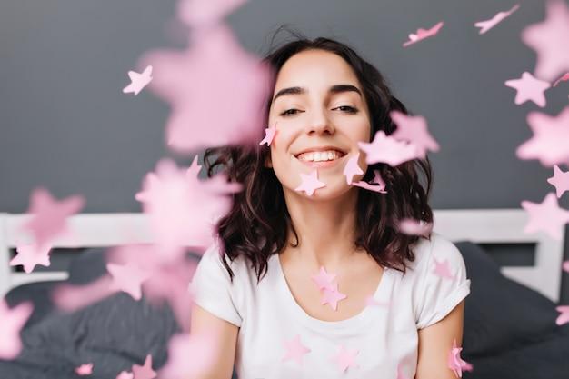 Retrato feliz emocionada joven morena en camiseta blanca divirtiéndose, sonriendo entre oropel rosa cayendo en la cama en apartamento moderno. expresando verdaderas emociones positivas, felicidad.