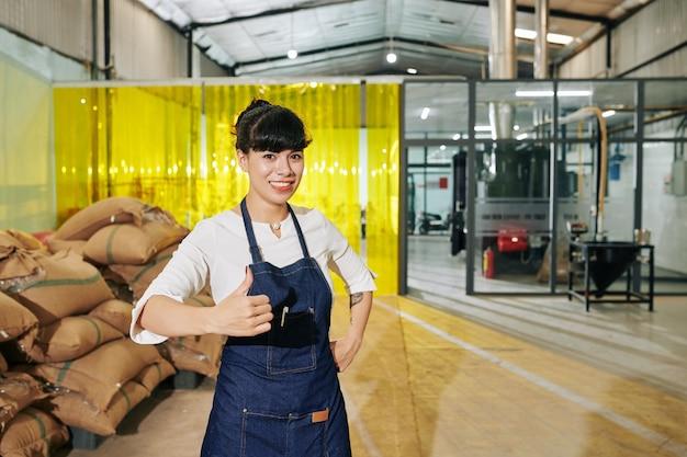 Retrato de feliz emocionado propietario tostador de café mostrando thumbs-up y mirando a la cámara